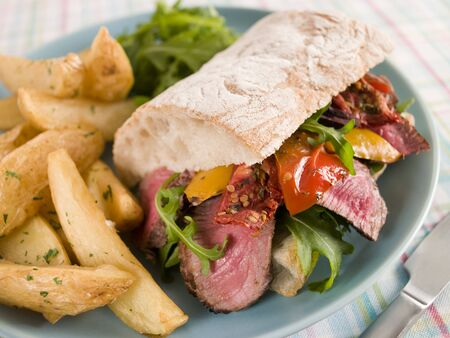 Steak and Roasted Pepper Ciabatta Sandwich with Spiced Potato Wedges photo