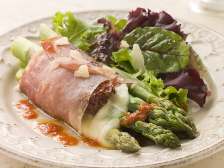 Roasted Asparagus spears with Mozzarella Cheese and Sun Dried Tomatoes wrapped in Prosciutto photo