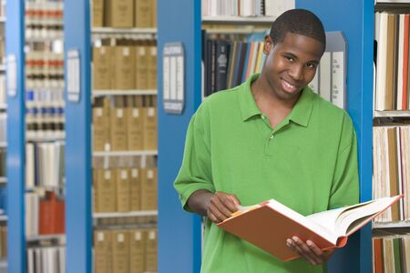 the field and in depth: Man in library holding book (depth of field) Stock Photo