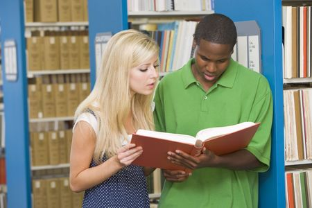 Man and woman in library reading book (depth of field) photo
