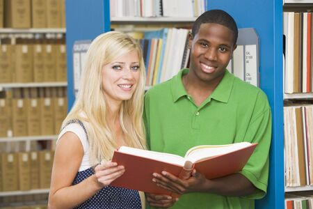 Man and woman in library holding book (depth of field) photo