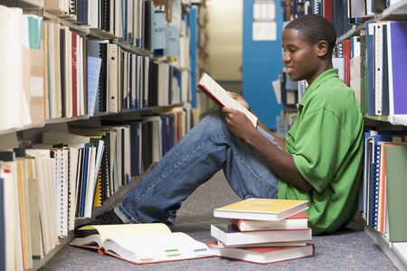library student: Man sitting on floor in library reading book Stock Photo