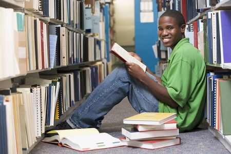 Man sitting on floor in library holding book photo