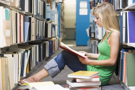 Woman sitting on floor in library reading book Stock Photo - 3201478