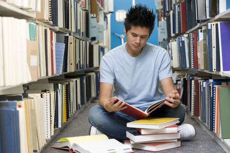 only one teenage boy: Man sitting on floor in library reading book Stock Photo