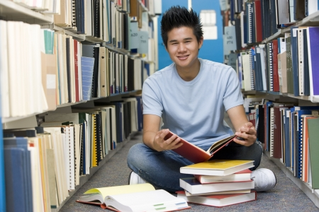 east asian ethnicity: Man sitting on floor in library holding book