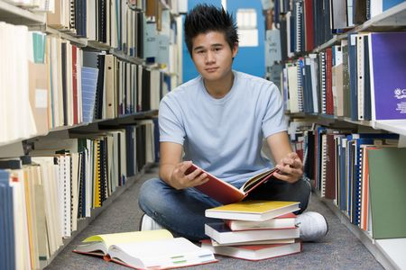 only one teenage boy: Man sitting on floor in library holding book