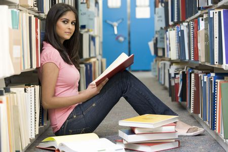 Woman sitting on floor in library holding book photo