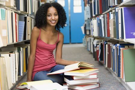 frontal views: Woman sitting on floor in library holding book Stock Photo