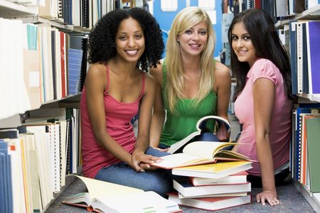 Three women sitting on floor in library with books photo