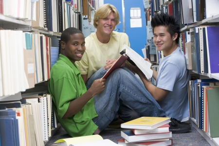 asian youth: Three men sitting on floor in library with books