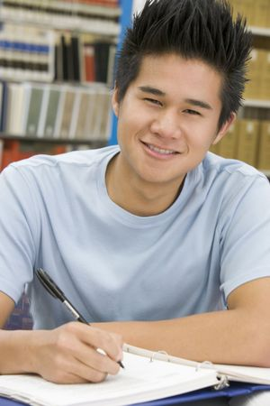 only one teenage boy: Man sitting in library studying