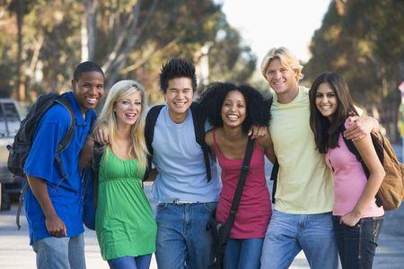 hispanic student: Seis personas de pie al aire libre del brazo juntos (atenci�n selectiva)