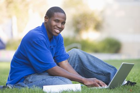 uses computer: Man outdoors sitting on grass with laptop (selective focus)