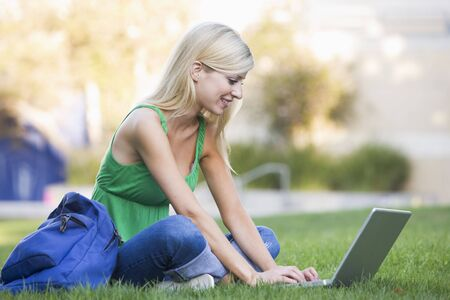 knap sack: Woman outdoors sitting on grass with laptop (selective focus)