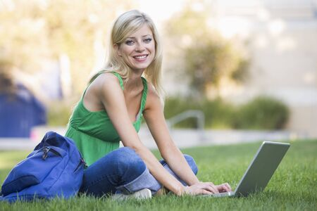 ruck sack: Woman outdoors sitting on grass with laptop (selective focus)