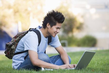 Man outdoors sitting on grass with laptop (selective focus) photo
