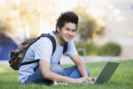Man outdoors sitting on grass with laptop (selective focus) Stock Photo - 3204879