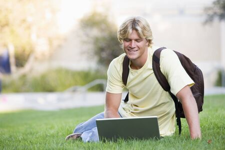 knap sack: Man outdoors sitting on grass with laptop (selective focus)