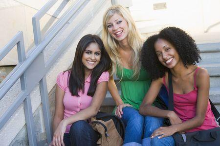 sorrisos: Três mulheres sentadas na escadaria ao ar livre, sorrindo, (high key)