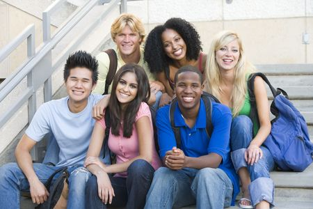 estudantes: Seis pessoas sentadas na escadaria ao ar livre sorrindo