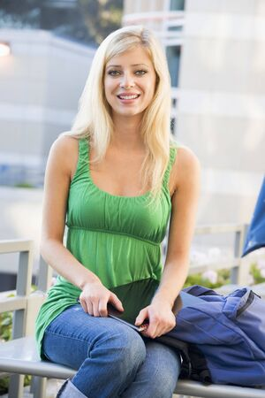 ruck sack: Woman sitting on bench outdoors with notebook smiling (selective focus) Stock Photo