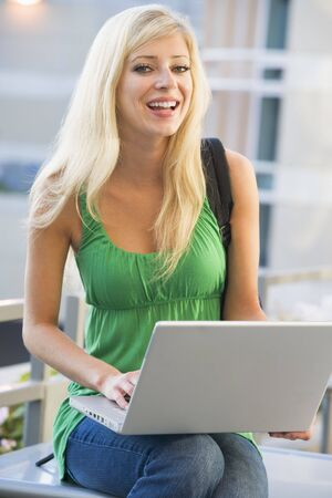 knap sack: Woman sitting on bench outdoors with laptop smiling (selective focus) Stock Photo