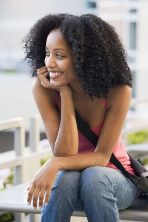 frontal views: Woman sitting on bench outdoors smiling (selective focus)
