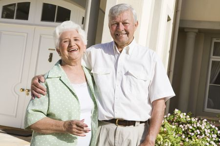 residence: Senior couple standing outside their home