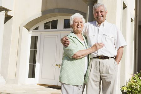 golden years series: Senior couple standing outside their home