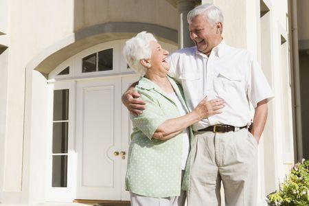 pareja madura feliz: Senior pareja de pie fuera de su casa