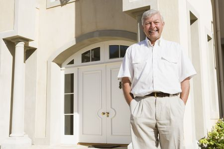 house series: Senior man standing outside his home Stock Photo