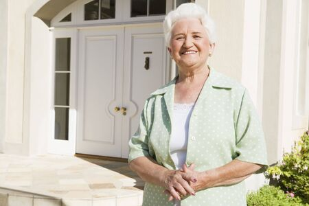 Senior woman standing outside her home Stock Photo