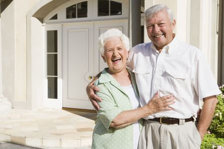 house series: Senior couple standing outside their home