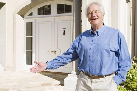 Senior man standing outside his home photo