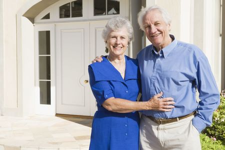 Senior couple standing outside their home photo