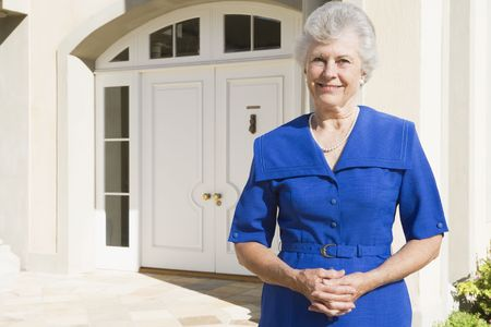 golden years series: Senior woman standing outside her home Stock Photo