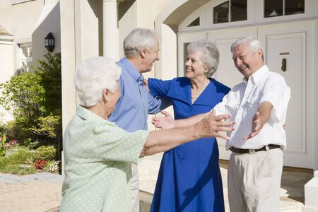 Two senior couples greeting each other with open arms photo