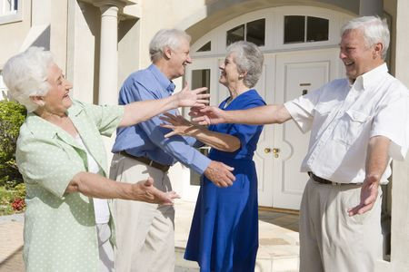 greet: Two senior couples greeting each other with open arms Stock Photo