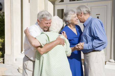 senior couples: Two senior couples greeting each other with open arms Stock Photo