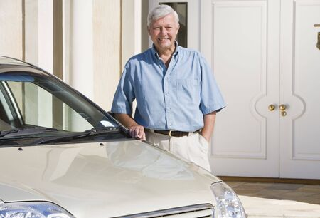 motorcars: Senior man standing with his car outside his home