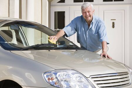 Senior man washing his car outside his home photo