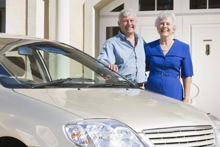 Senior couple standing with their car outside their home photo