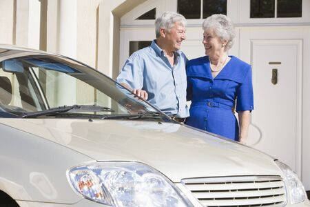 motorcars: Senior couple standing with their car outside their home Stock Photo
