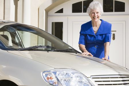 motorcars: Senior woman standing with her car outside her home