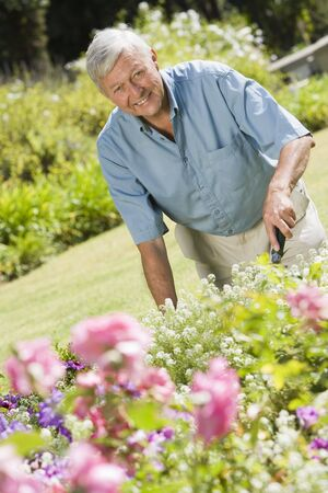 offset view: Senior man in a flower garden