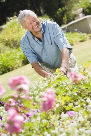 Senior man in a flower garden photo