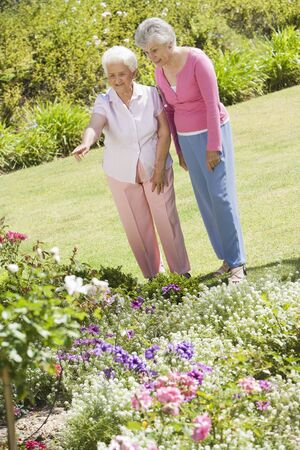 Two senior women in a flower garden photo
