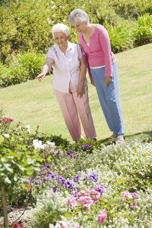 offset angles: Two senior women in a flower garden