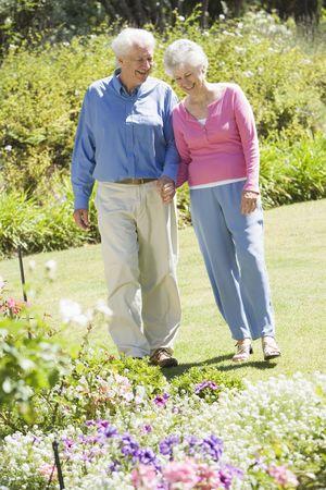 senioren wandelen: Senior paar in een bloementuin
